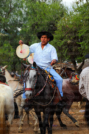 Gaucho riding horse and playing caja (drum) during carnival parades, Canasmoro, Tarija Department, Bolivia