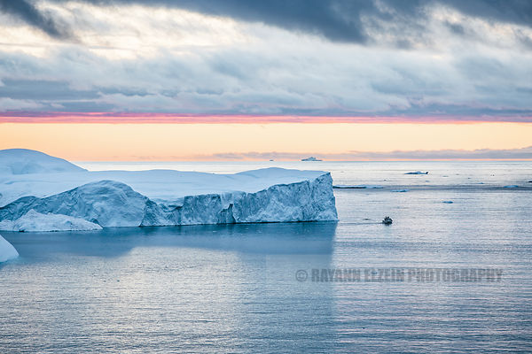 Fishing boat and massive icebergs at sunset
