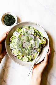 Creamy Cucumber Salad in a ceramic bowl on a marble work surface
