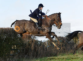 Annabel Neasham jumping a hedge near Hill Top Farm