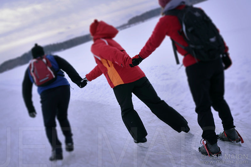 3 young adults ice-skating hand-in-hand