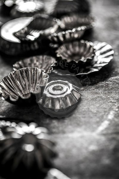 Black and white antique candy tins styled on a rustic tin surface.