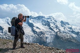 Man with reflex camera  photographing snow covered mountains