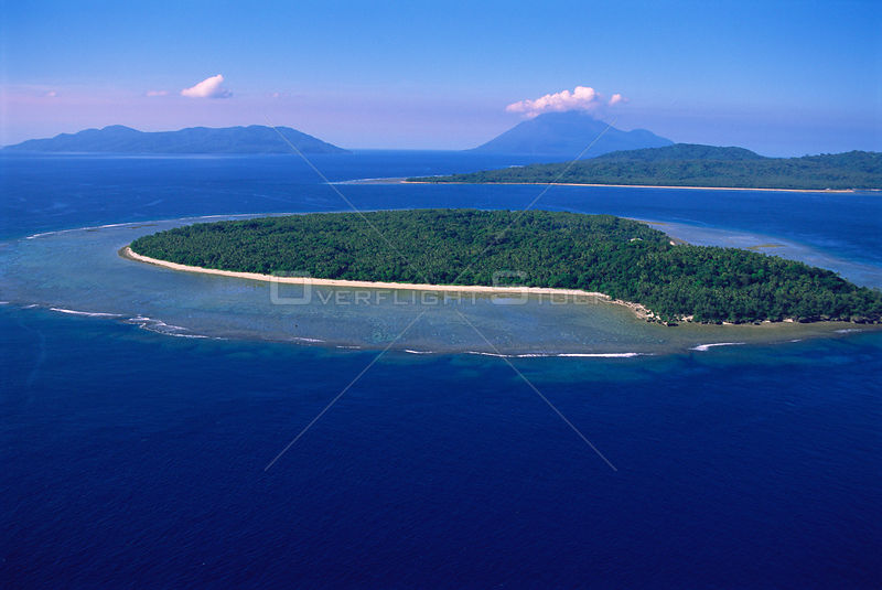Aerial view of Lamen Island with fringing reef, high volcanic islands in background (Epi, Lopevi and Paama Is) Vanuatu, South Pacific