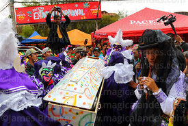 "A cholita wearing a black veil (to symbolise mourning) accompanies the pepino in his coffin as he is  ""buried"" during parades for the Entierro del Pepino, La Paz, Bolivia"