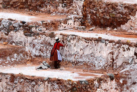 Quechua woman repairing wall of salt evaporation terrace at Las Salineras, Maras, near Cusco, Peru