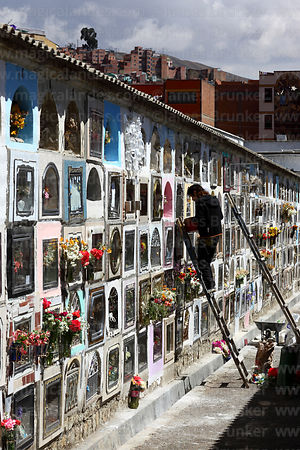 Person preparing tomb in cemetery for Todos Santos festival, La Paz, Bolivia