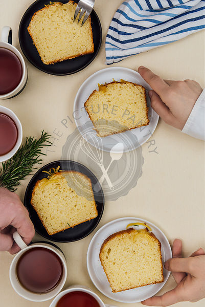 People grabbing kefir lemon bread slices served on plates and tea from a breakfast table photographed from top view.