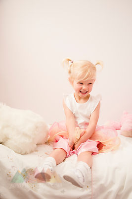 Portrait of laughing little girl sitting on bed