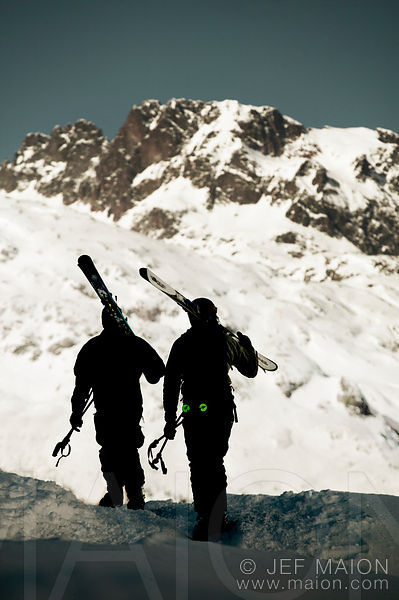 Skier silhouettes carrying skis and mountain
