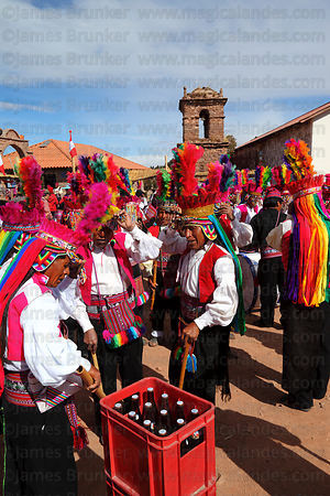 Beer break between dances at San Santiago festival , Taquile Island , Peru