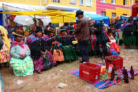 Man serving beer to Aymara women at festival in Caquiaviri, Bolivia
