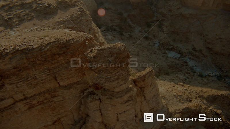 Aerial close up sides of rocky outcrop and around single weathered pillar of rock with desert terrain below Fish River Canyon Namibia