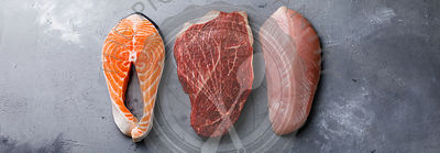 Raw food Salmon oily fish steak, beef meat and chicken breast on gray concrete background