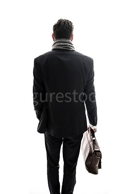 A mystery man in a suit, walking away and carrying a bag – shot from eye level.