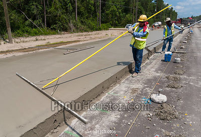 Highway construction workers smooth out freshly poured concrete using trowels on a new span of road