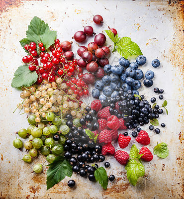 Mix of fresh berries with leaves on textured metal background