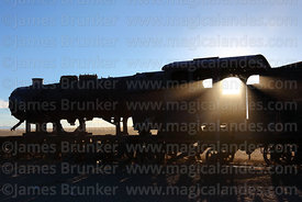 Old steam train in train cemetery silhouetted against sun, Uyuni, Bolivia