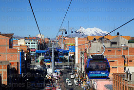 Blue Line cable car cabin with Mar para Bolivia / Sea for Bolivia slogan on it and Av Chacaltaya station, Mt Illimani in background, El Alto, Bolivia