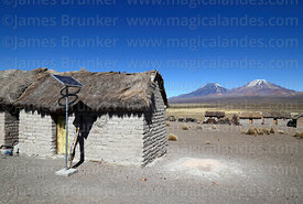 Solar panel next to thatched adobe house in Estancia Huincurata, Payachatas volcanos in background, Sajama National Park, Bolivia