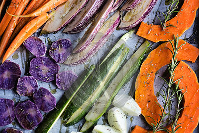 Chopped raw vegetables on baking sheet before roasting. Top view, Food background