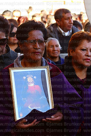 A member of the brotherhood of Señor de las Caidas / The Fallen Christ carries a picture of Jesus during Good Friday procession, La Paz, Bolivia