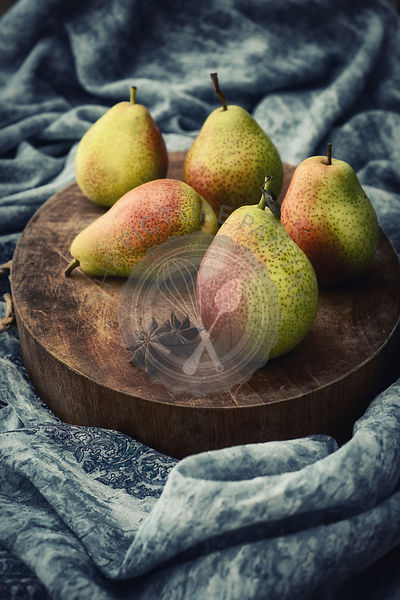 Five pears on a chopping board with rustic setup and styling.