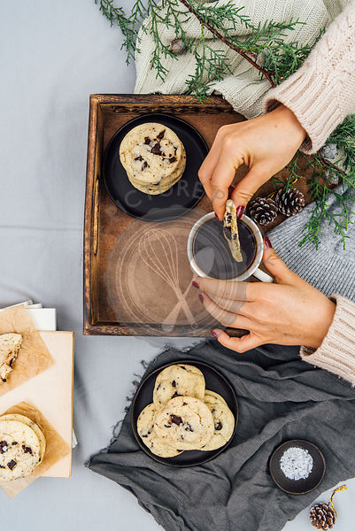 A woman dipping a chocolate chip cookie into her coffee in a wooden tray photographed from top view. More cookies on a black plate and on some books, pine tree branches and a small bowl of sea salt accompany.
