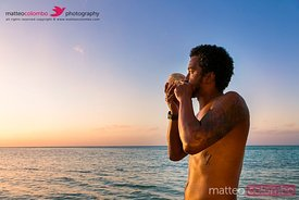 Local man blowing traditional conch shell at sunset, Fiji