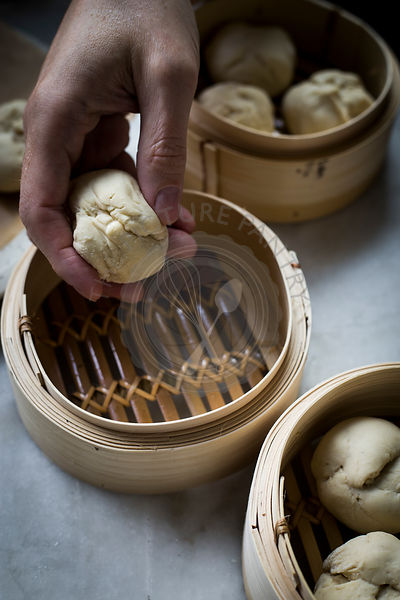 Man's hand placing dumpling in a steamer on marble tabletop