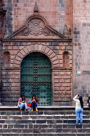 Girl taking photo with camera phone in front of right entrance of cathedral, Cusco, Peru