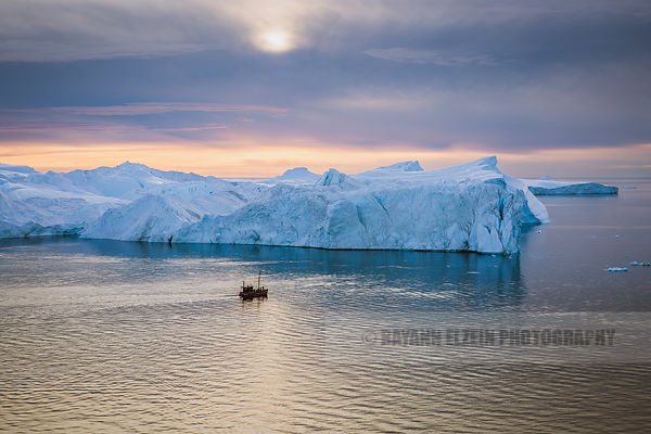 Boat showing tourists the beauty of the icebergs of the Ilulissat Icefjord from nearby