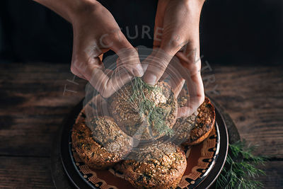 Persons Hands wth Corn muffins bread with leaf of chard