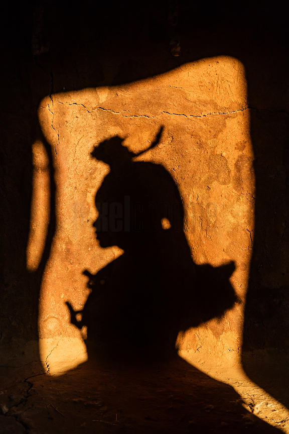 Shadow of a Himba Woman in the Doorway of her Hut at Sunset