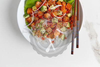 Salmon Poke photographed from above in a white bowl on a white marble surface.