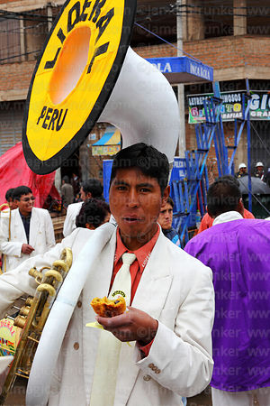 Sousaphone player eating salteña snack at Virgen de la Candelaria festival, Puno, Peru