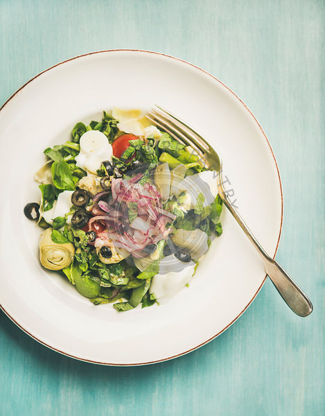 Fresh green summer salad with artichokes over blue wooden background