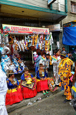 A ch'uta and cholitas outside a shop that sells and rents festival costumes, La Paz, Bolivia