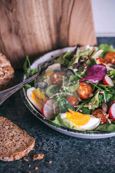 Salad with mixed greens, cherry tomatoes and eggs in a serving bowl