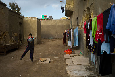 Egypt - Cairo - Boys play football in the street whilst a woman hangs washing on a line to dry in the Northern cemetery area known as the City of the Dead.