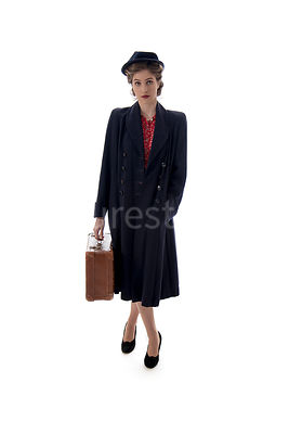 A 1940's woman in a hat and a coat, carrying a suitcase – shot from eye-level.