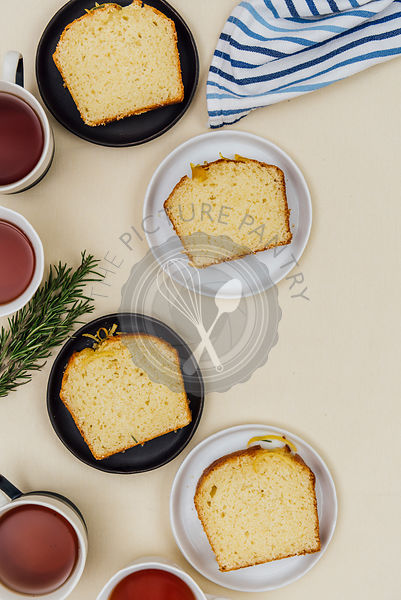 Kefir lemon bread slices served on black and white plates photographed from top view. Tea cups accompany.