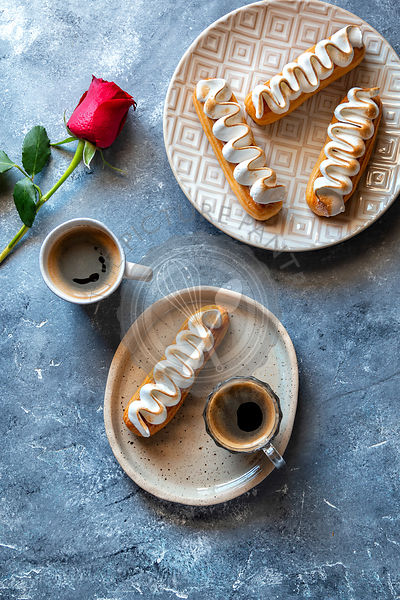 French eclairs and 2 cups of coffee on the table