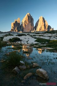 Famous three peaks at sunrise reflected in water Dolomites Italy