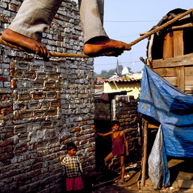 A performer practices his tightrope walking act in the slums of Kathputli