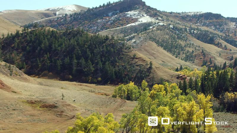 Bright red rock formations stand above a narrow valley filled with autumn colored trees