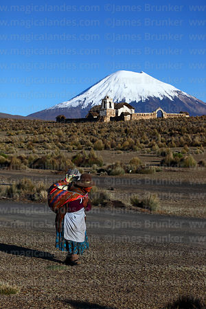 Old Aymara woman walking along dirt track, rustic church  and Parinacota volcano behind, Lagunas, Sajama National Park, Bolivia