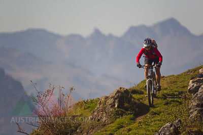 Austria, Tirol, Female mountain biker biking on spitzstein mountain