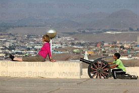 Boy playing with cannon on El Morro headland, Arica, Region XV, Chile
