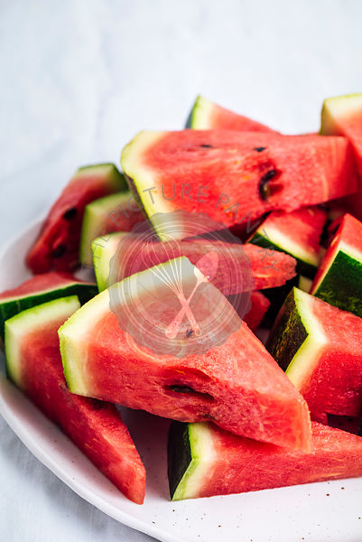 Mini watermelon slices in triangle shape are piled on a plate.